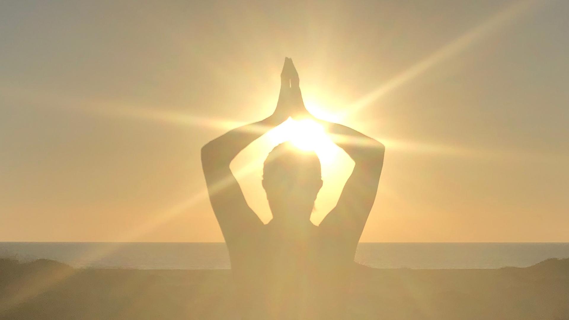 insegnante di yoga controsole al mare che pratica